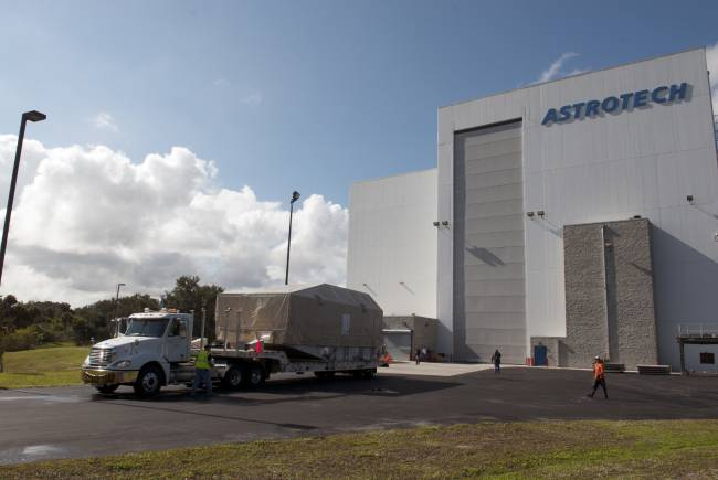 A truck hauls NASA's TDRS-L satellite to the Astrotech facility in Titusville for launch processing. The TDRS is the latest spacecraft destined for the agency's constellation of communications satellites that allows nearly continuous contact with orbiting spacecraft ranging from the International Space Station and Hubble Space Telescope to the array of scientific observatories. Photo credit: NASA/Charisse Nahser