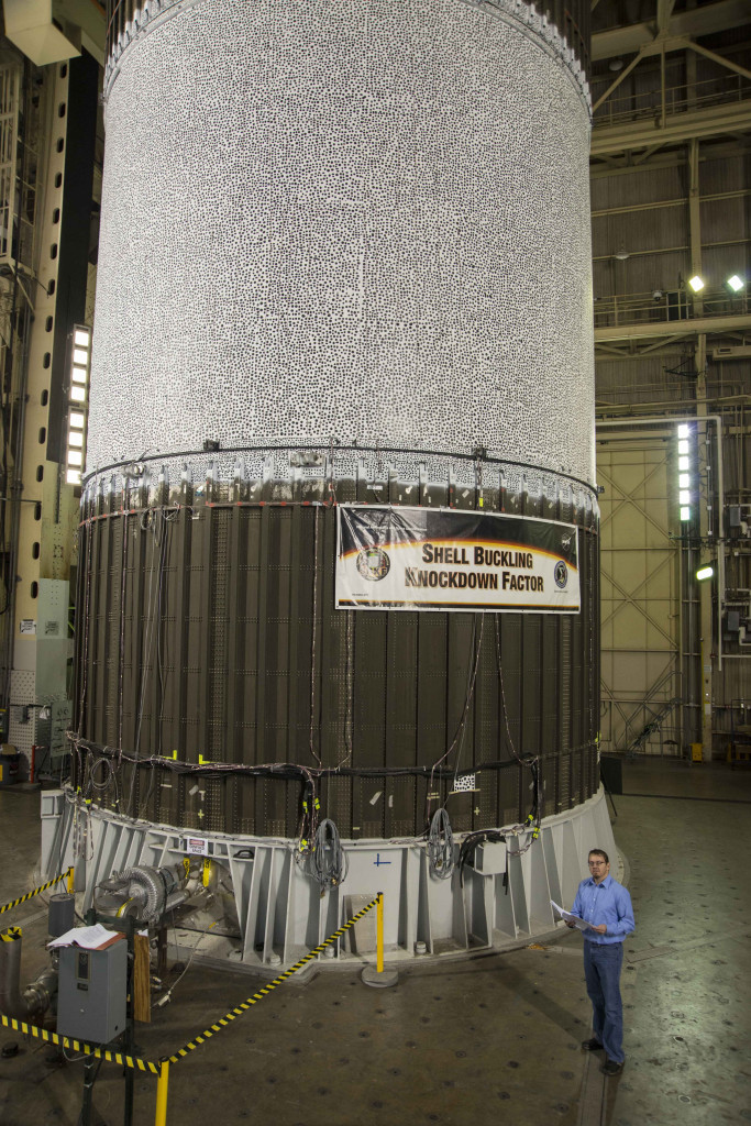 NASA's Mark Hilburger prepares to buckle an aluminum-lithium cylinder about the size of fuel tank barrels for the largest rockets ever built. The black and white dots on the upper portion of the tank helped 20 high-speed cameras record minute changes in the tank as almost a million pounds of force pressed down upon the tank in a test at NASA's Marshall Space Flight Center. Image Credit: NASA/Fred Deaton
