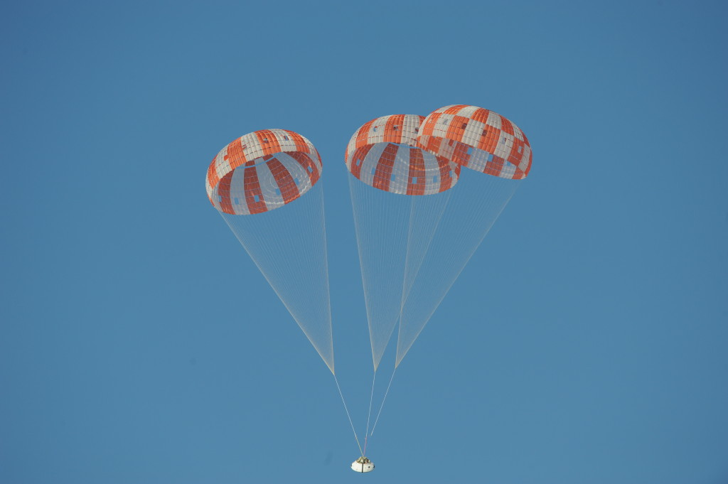 A test version of Orion descends under its three massive main parachutes, which together would cover almost all of a football field. Image Credit: NASA