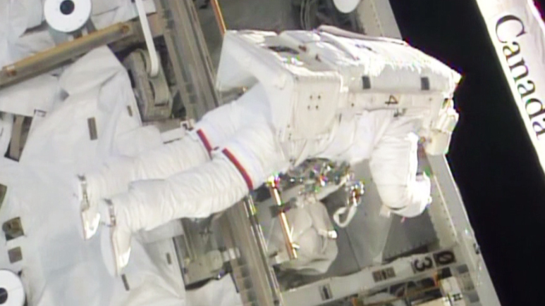 A spacewalker works on the S0 truss after replacing a failed backup computer. Image Credit: NASA TV