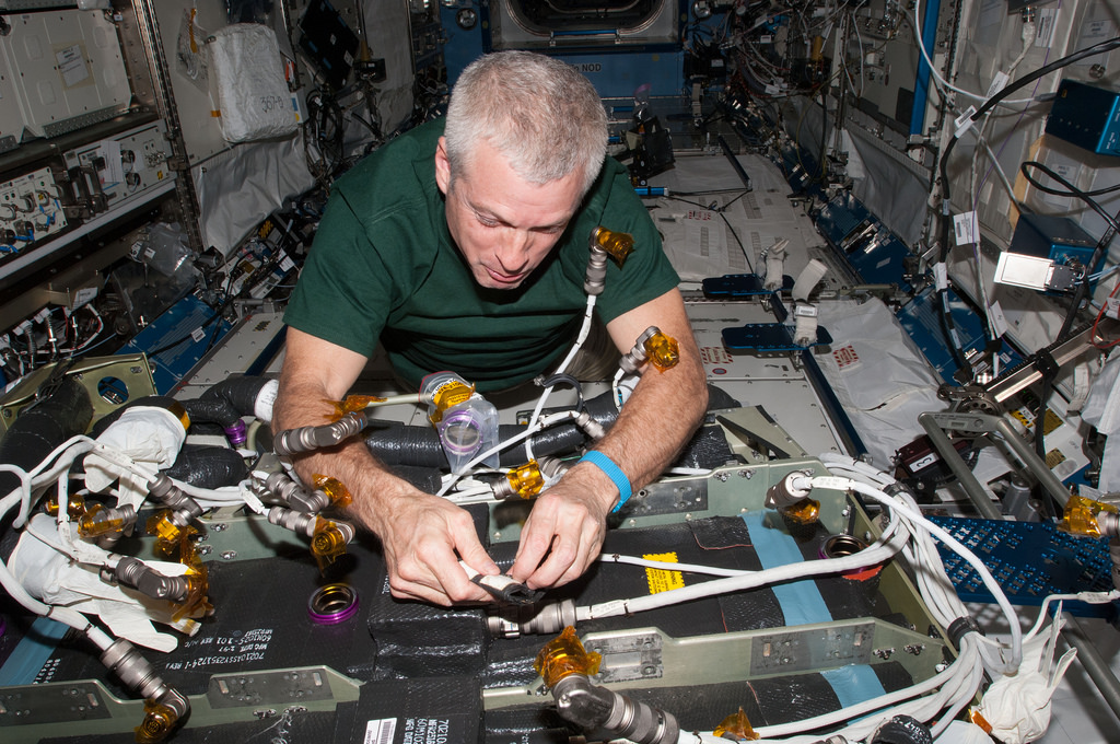 Astronaut Steve Swanson works during in-flight maintenance to mate electrical connectors in Tranquility's Carbon Dioxide Removal Assembly (CDRA). Image Source: NASA