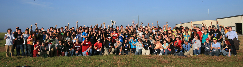 Following the launch of the RockOn sounding rocket, the students and teachers who built the payload posed for a group photo and signal thumbs-up to a successful launch. Credit: NASA/G. Qian
