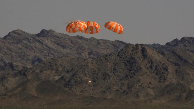 A test version of NASA's Orion spacecraft descends under its three main parachutes above the U.S. Army Proving Ground in Arizona in the agency's most difficult test of the parachutes system's performance. Image Credit: NASA/Rad Sinyak
