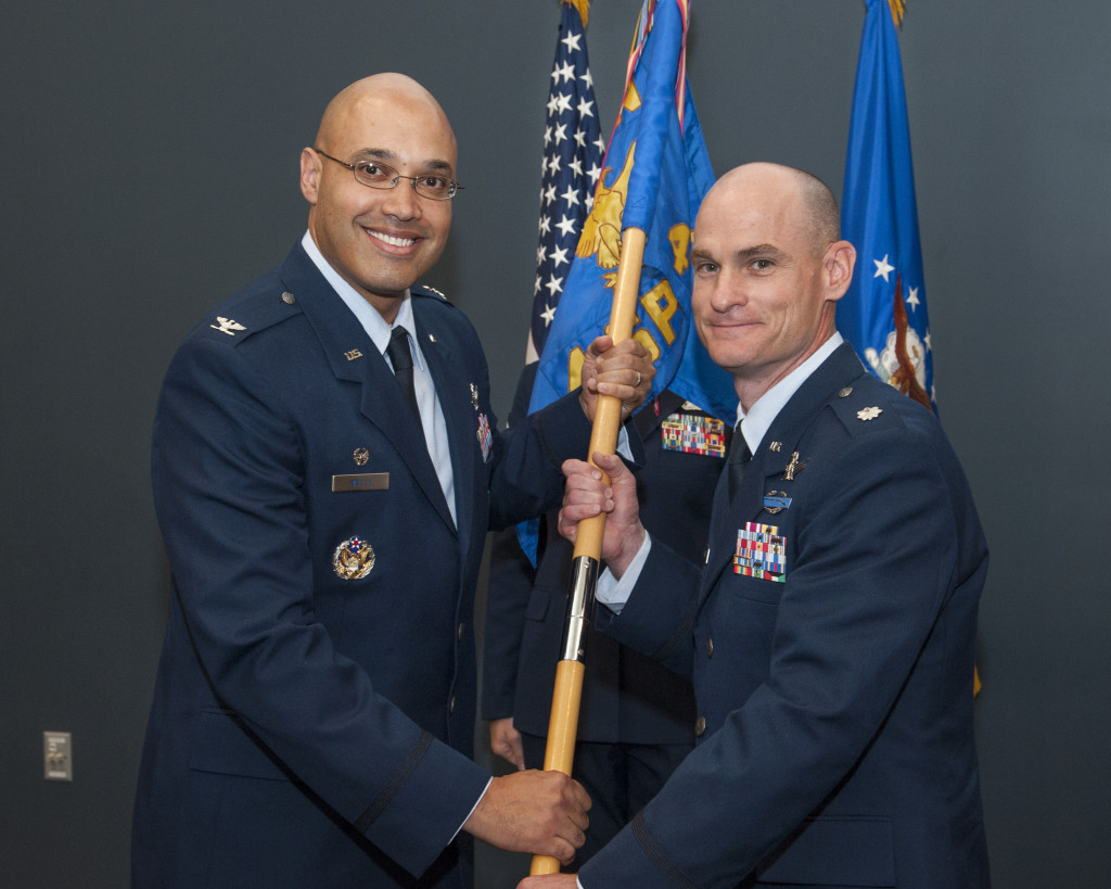 Col. David Miller Jr. (left), 21st Operations Group commander, passes the 4th Space Control Squadron guidon to Lt. Col. Eric Lingle, 4th SPCS commander, during the squadron's change of command ceremony on July 11. Image Source: U.S. Air Force photo/Craig Denton