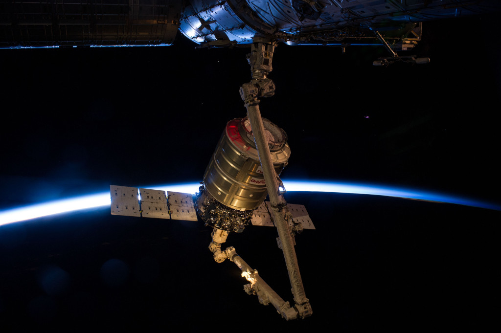 ntersecting the thin line of Earth's atmosphere, the Orbital Sciences' Cygnus cargo craft attached to the end of the Canadarm2 robotic arm of the International Space Station is photographed by an Expedition 40 crew member after the two spacecraft converged at 6:36 a.m. EDT Wednesday. Image Credit: NASA