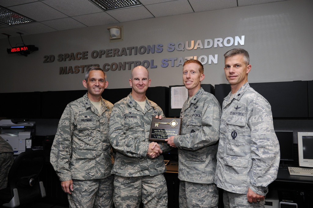 Col. Dennis Bythewood, 50th Operations Group commander, transfers command and control of the seventh GPS Block IIF satellite to Lt. Col. Todd Benson, 2nd Space Operations Squadron commander, Aug. 8 at Schriever Air Force Base, Colorado. Col. Damon Feltman, 310th Space Wing commander (left), and Lt. Col. Stephen Slade, 19th Space Operations Squadron commander (right), also participated in the transfer ceremony. Members of 2 SOPS and 19 SOPS operate the GPS constellation.  Image Source: Schriever Air Force Base