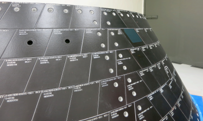 Two one-inch-wide holes have been drilled into tiles on Orion's back shell to simulate micrometeoroid orbital debris damage . Image Credit: NASA