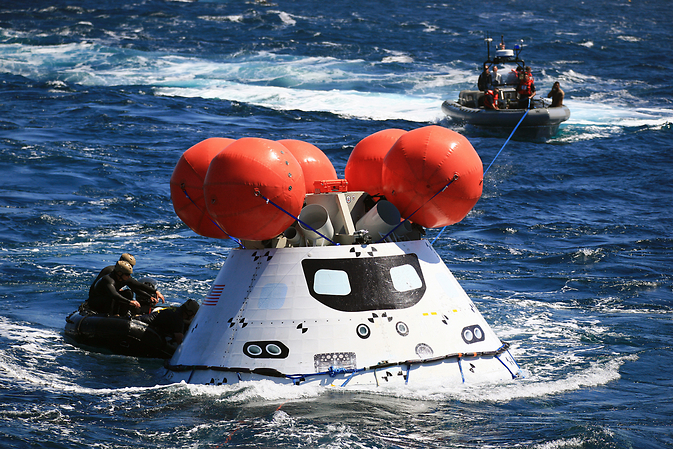 The Orion boilerplate test vehicle floated in the Pacific Ocean, near the USS Anchorage on Sept. 17, during the third day of Underway Recovery Test 3. U.S. Navy divers in a Zodiac boat, at left, and other team members in a rigid hull inflatable boat prepared the test vehicle for return to the ship. Image Credit: NASA/Kim Shiflett