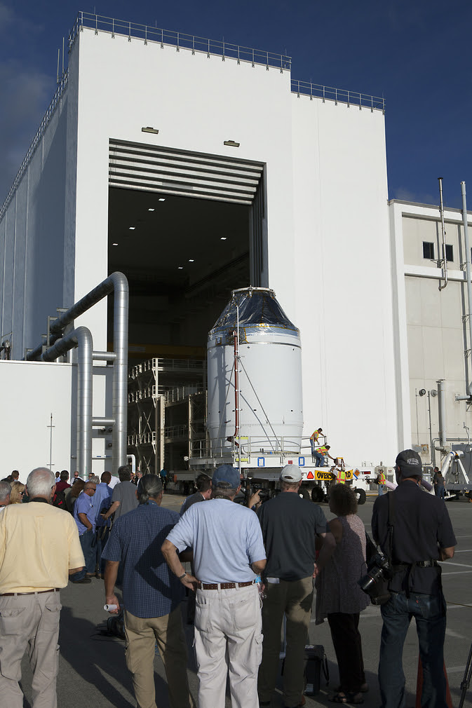 The Orion crew module, stacked atop its service module, moved out of the Neil Armstrong Operations and Checkout Building at NASA's Kennedy Space Center in Florida on Sept 11. Orion was transported to the Payload Hazardous Servicing Facility at Kennedy where it will be fueled ahead of its December flight test.  Image Credit: NASA/Dan Casper