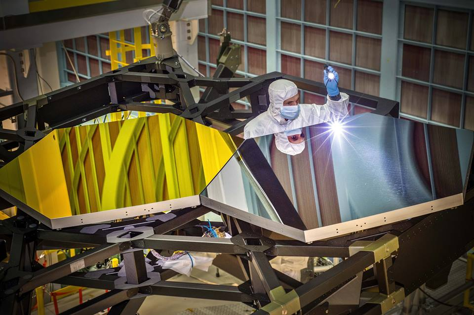 A Ball Aerospace & Technologies Optical Engineer inspects test mirror segments for the James Webb Space Telescope. Image Credit: Ball Aerospace & Technologies