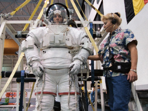 Astronaut Janet L. Kavandi, mission specialist, is about to be lowered into a deep pool for an underwater training session. The training took place at the Johnson Space Center's Neutral Buoyancy Laboratory (NBL), part of the Sonny Carter Training Center. Kavandi has weights on the training version of her extravehicular mobility unit (EMU) which help to provide neutral buoyancy in the pool. Astronauts Kavandi and Gerhard P.J. Thiele were participating in a rehearsal of a contingency space walk for the STS-99 mission. Image Credit: NASA