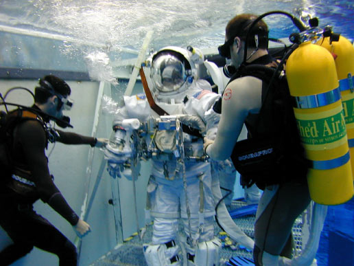 JSC2002-E-27793 (2002) --- Astronaut Barbara R. Morgan, wearing a training version of the Extravehicular Mobility Unit (EMU) spacesuit, participates in an underwater simulation of extravehicular activity (EVA) at the Neutral Buoyancy Laboratory (NBL) near Johnson Space Center (JSC). Divers assisted Morgan. Image Credit: NASA
