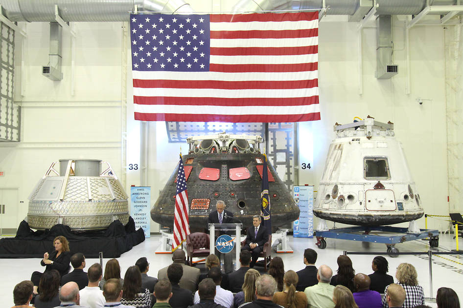 "In the Neil Armstrong Operations and Checkout Building high bay at NASA's Kennedy Space Center in Florida, NASA Administrator Charles Bolden delivers a ""state of the agency"" address on Feb. 2, 2015 at NASA's televised fiscal year 2016 budget rollout event with Kennedy Space Center Director Bob Cabana looking on, at right. NASA's Orion, SpaceX Dragon and Boeing CST-100 spacecraft, all destined to play a role in NASA's overall exploration objectives, were on display. Image credit: NASA/Amber Watson"