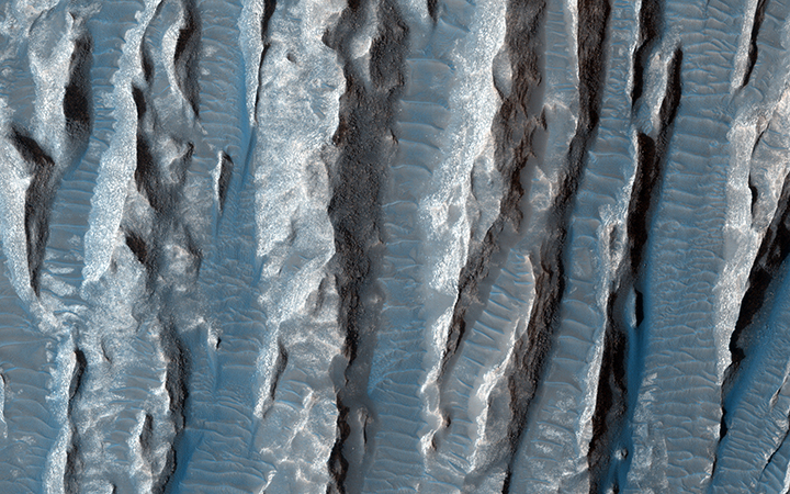 This view of Martian surface features shaped by effects of winds was captured by the HiRISE camera on NASA's Mars Reconnaissance Orbiter on January 4, 2015. Image Credit: NASA/JPL-Caltech/Univ. of Arizona