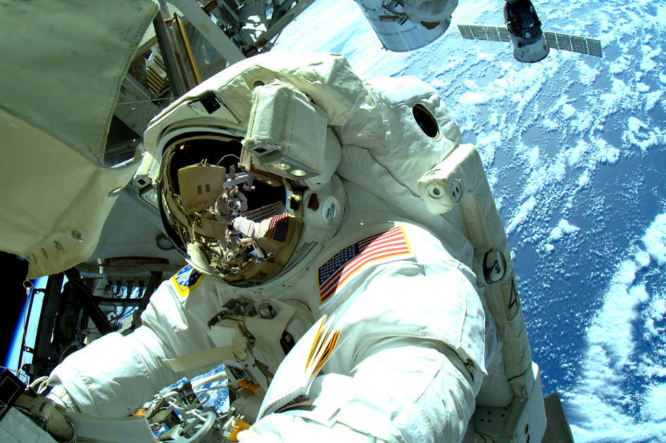 "Terry Virts tweeted this photograph and wrote, ""Out on the P3 truss. #AstroButch handing me his cable to install on the new antenna. #spacewalk"" Image Credit: NASA"