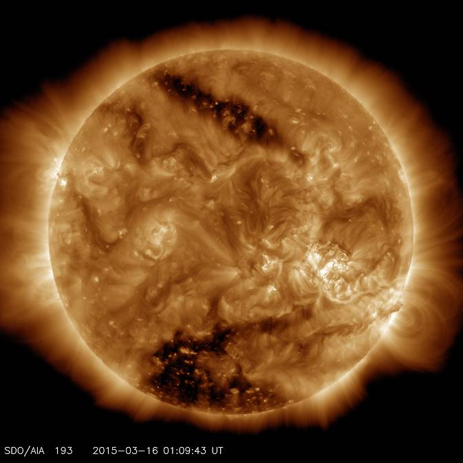 This image from NASA's Solar Dynamics Observatory on March 16, 2015, shows two dark spots, called coronal holes. The lower coronal hole was one of the biggest observed in decades. Image Credit: NASA/SDO