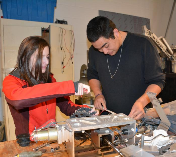 Mechanical engineering student Kaitlyn Martin and electrical engineering student Eduardo Urquidi Junior are taking apart last year's rover. Image Credit: Colorado School of Mines