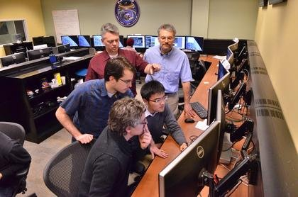 Undergraduate students, foreground left to right, Lucas Migliorini, Matt Muszynski and Hui Kang Ma work in the MMS control room in LASP at the University of Colorado Boulder under the direction of MMS Flight Director Jason Beech, background left, and MMS Science Operations Center Manager Chris Pankratz.  Image Credit: Casey A. Cass/University of Colorado