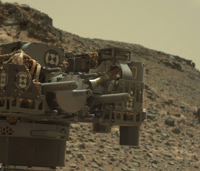 "This raw-color view from Curiosity's Mastcam shows the rover's drill just after finishing a drilling operation at ""Telegraph Peak"" on Feb. 24, 2015. Image Credit: NASA/JPL-Caltech/MSSS"