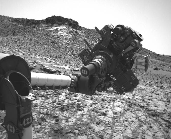 This March 4, 2015, image from the Navcam on NASA's Curiosity Mars rover shows the position in which the rover held its arm for several days after a transient short circuit triggered onboard fault-protection programming to halt arm activities on Feb. 27. Image Credit: NASA/JPL-Caltech/MSSS