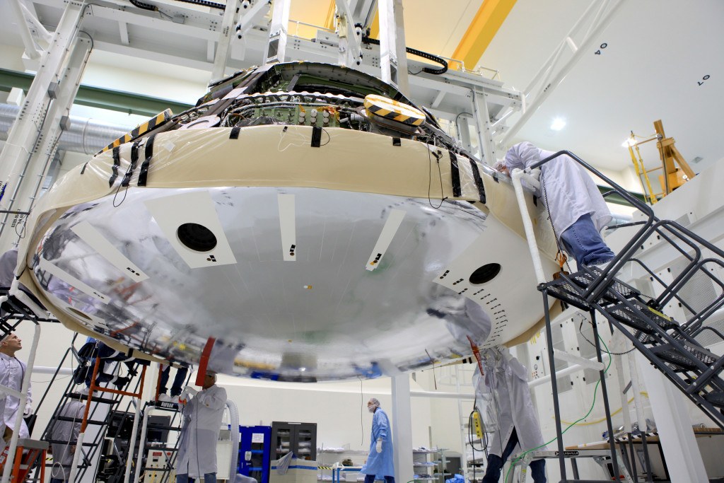 Orion, NASA's new exploration spacecraft, being prepared for its first flight test. The 10-inch holes on the bottom of the spacecraft designate placement of the compression pads. Image Credit: NASA