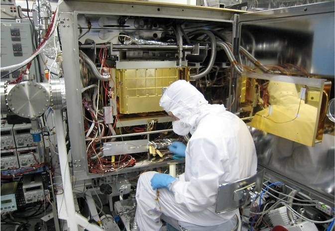 A Sample Analysis at Mars (SAM) team member at NASA Goddard prepares the SAM testbed for an experiment. This test copy of the SAM suite of instruments is inside a chamber that, when closed, can model the pressure and temperature environment that SAM sees inside Curiosity on Mars. Image Credit: NASA