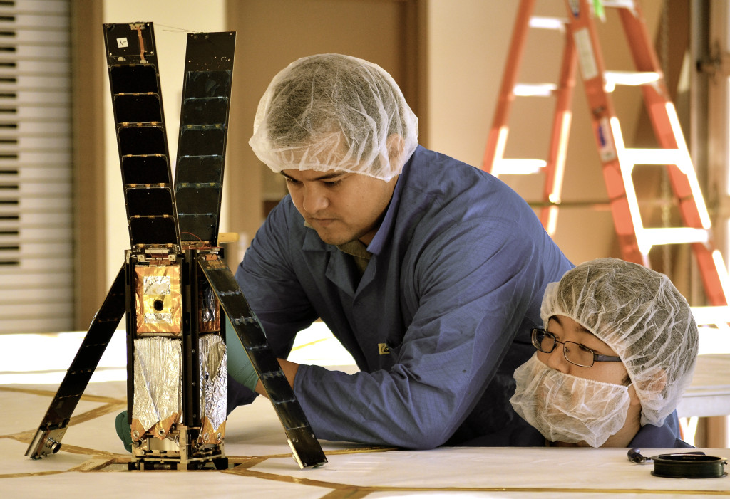 LightSail team members Alex Diaz and Riki Munakata prepare the spacecraft for a sail deployment test. Image Credit: The Planetary Society