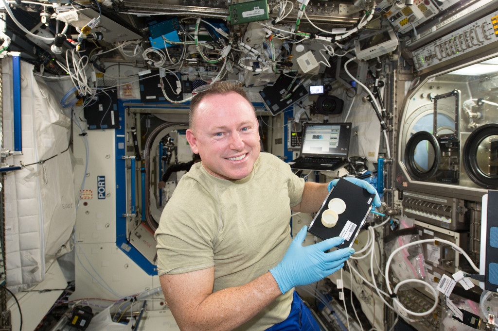 NASA astronaut Butch Wilmore holds a container, the first object with two parts, a lid and container, printed in space. Image Credit: NASA