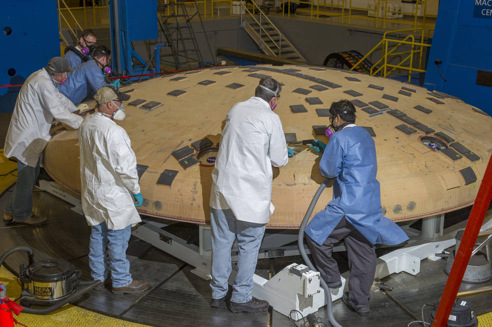Engineers from NASA's Ames Research Center in Moffett Field, California, and NASA's Marshall Space Flight Center in Huntsville, Alabama, remove segments of a heat-resistant material called Avcoat from the surface of the Orion heat shield, the protective shell designed to help the next-generation crew module and its future occupants withstand the heat of atmospheric reentry. The work is being conducted in the seven-axis milling machine facility at Marshall. Image Credit: NASA/MSFC/Emmett Given