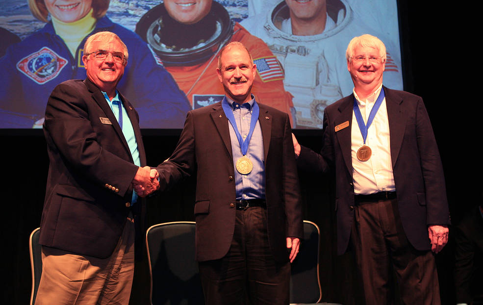 NASA Associate Administrator for the Science Mission Directorate and astronaut John Grunsfeld (center) is inducted into the U.S. Astronaut Hall of Fame on May 30, 2015 at the NASA Kennedy Space Center Visitor Complex in Florida. Shaking Grunsfeld's hand is Dan Brandenstein, Chairman of the board of directors for the Astronaut Scholarship Foundation, and standing next to Grunsfeld is former NASA astronaut Steve Hawley. Image Credit: NASA