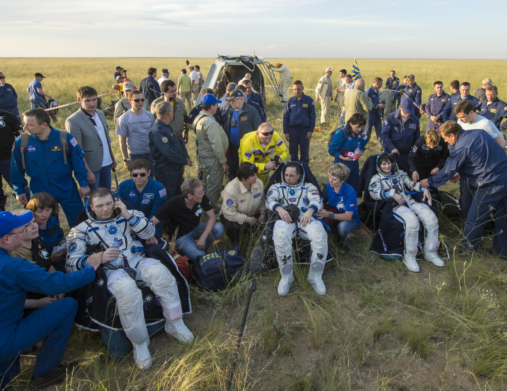 Expedition 43 commander Terry Virts of NASA, left, cosmonaut Anton Shkaplerov of the Russian Federal Space Agency (Roscosmos), center, and Italian astronaut Samantha Cristoforetti from European Space Agency (ESA) sit in chairs outside the Soyuz TMA-15M spacecraft just minutes after they landed in a remote area near the town of Zhezkazgan, Kazakhstan on Thursday, June 11, 2015. Image Credit: NASA/Bill Ingalls