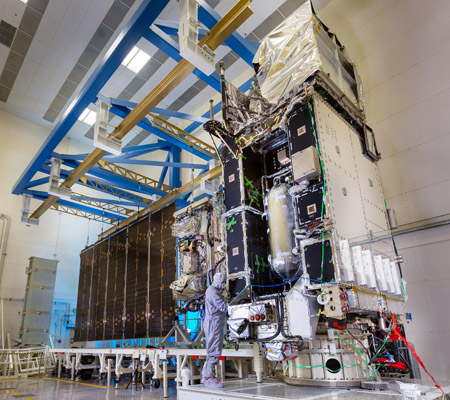 NOAA's GOES-R weather satellite is being connected to its large solar array in a Lockheed Martin clean room. Image Credit: Lockheed Martin