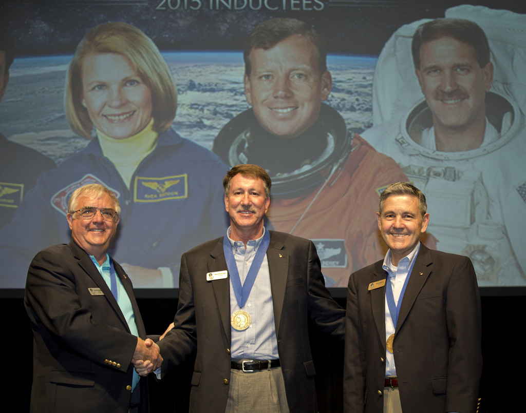 Astronaut Dan Brandenstein and Kennedy Space Center Director, Bob Cabana, welcome 2015 AHOF Inductee, Kent Rominger, into the U.S. Astronaut Hall of Fame Induction. Image Credit: Kennedy Space Center Visitor Complex
