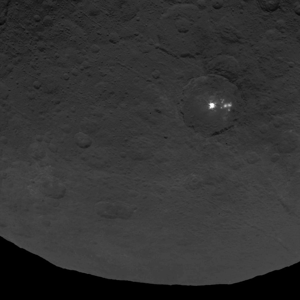 A cluster of mysterious bright spots on dwarf planet Ceres can be seen in this image, taken by NASA's Dawn spacecraft from an altitude of 2,700 miles (4,400 kilometers). The image, with a resolution of 1,400 feet (410 meters) per pixel, was taken on June 9, 2015. Image credit: NASA/JPL-Caltech/UCLA/MPS/DLR/IDA