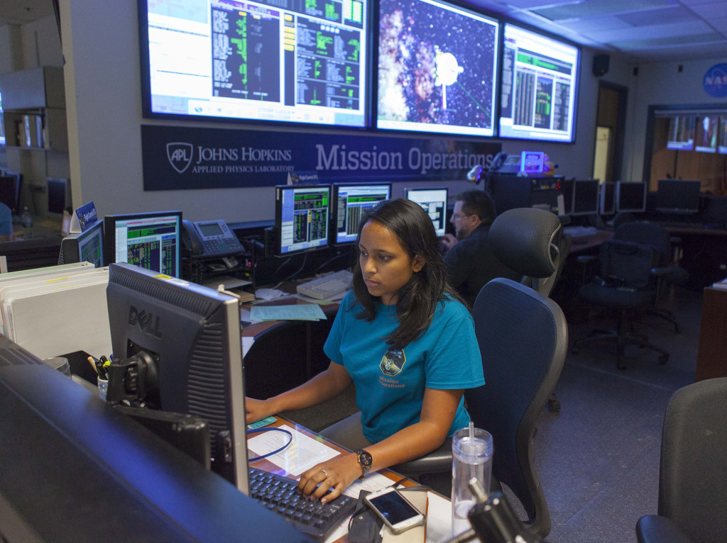 In the New Horizons Mission Operations Center at the Johns Hopkins University Applied Physics Laboratory in Laurel, Maryland, Priya Dharmavaram (front) and Tim Miralles monitor telemetry from New Horizons following a course-correction maneuver on June 14 that refined the NASA spacecraft's path toward the Pluto system. Image Credit: Johns Hopkins University Applied Physics Laboratory