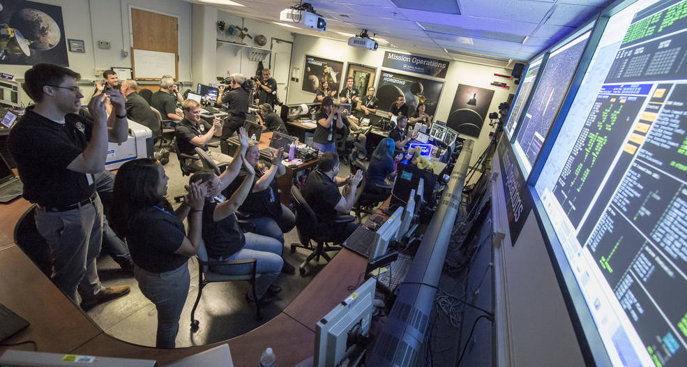 New Horizons Flight Controllers celebrate after they received confirmation from the spacecraft that it had successfully completed the flyby of Pluto, Tuesday, July 14, 2015 in the Mission Operations Center (MOC) of the Johns Hopkins University Applied Physics Laboratory (APL), Laurel, Maryland. Image Credit: NASA/Bill Ingalls