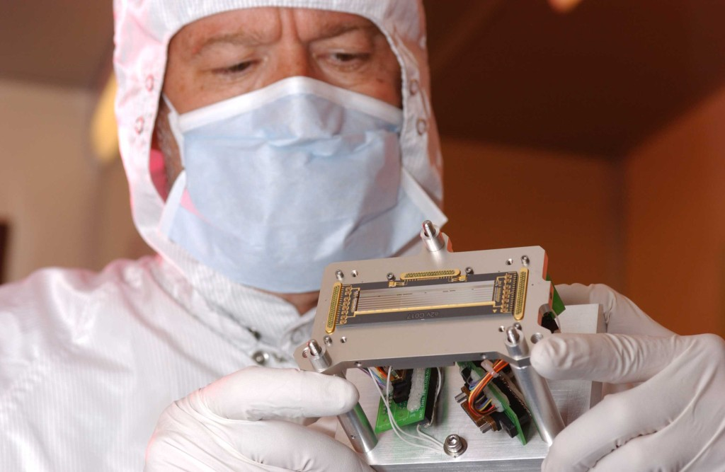 "Ball engineer Rick Taylor examines a component of Ralph, the ""eyes"" of the New Horizons mission. Ralph's suite of detectors will provide resolution 10 times better than the human eye. Image Credit: Ball Aerospace"