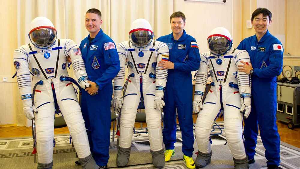 Expedition 44 crew members Kjell Lindgren , Oleg Kononenko and Kimiya Yui pose with their Sokol launch and entry suits July 11 at the Baikonur Cosmodrome in Kazakhstan. Image Credit: Gagarin Cosmonaut Training Center