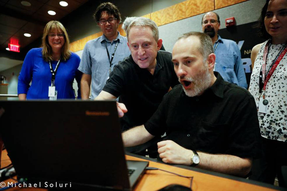 Science team members react to the latest image of Pluto at the Johns Hopkins University Applied Physics Lab on July 10, 2015. Left to right: Cathy Olkin, Jason Cook, Alan Stern, Will Grundy, Casey Lisse, and Carly Howett. Image Credit: Michael Soluri