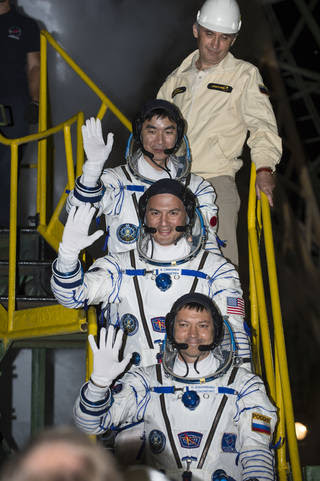 Expedition 44 Flight Engineer Kimiya Yui, of the Japan Aerospace Exploration Agency (JAXA), top; Flight Engineer Kjell Lindgren of NASA, center, and Soyuz Commander Oleg Kononenko of the Russian Federal Space Agency (Roscosmos), bottom, wave farewell prior to boarding the Soyuz TMA-17M spacecraft for launch, Thursday, July 23, 2015 at the Baikonur Cosmodrome in Kazakhstan. Kononenko, Lindgren, and Yui will spend the next five months aboard the International Space Station. Image Credit: (NASA/Aubrey Gemignani)