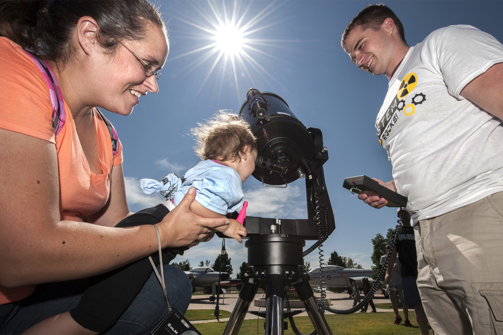 Second Lt. Michael Hintzman, Air Force Life Cycle Management Center, aims a large telescope at the sun while Melisa Hernandez-Morales holds Elienid Rivera up to view the sun through a special filter at STEM Rocks! 2013. This year, the festival will be held held from 10 a.m. to 2 p.m., Saturday, Aug. 29, 2015, at the Peterson Air and Space Museum. Image Credit: U.S. Air Force photo/Craig Denton