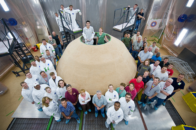 Lockheed Martin employees from Denver and New Orleans worked together to pack the thermal protective material on the back shell of the Mars Science Laboratory aeroshell. The biconic-shaped back shell is covered with a thermal protection system composed of the cork/silicone super light ablator that was created for the Mars Viking landers of the 1970s and has been used on every Lockheed Martin-built Mars aeroshell since. Image Credit: Lockheed Martin