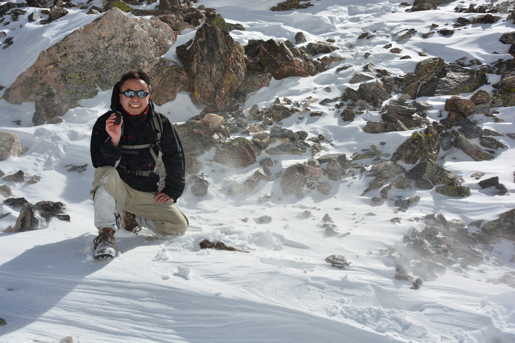 Senior Research Scientist Dr. Constantine Tsang examines a rock during a winter hike in Rocky Mountain National Park, Colorado, taken while the cloud conditions, high winds, and frozen lakes simulated an expedition to Antarctica. Image Credit: Constantine Tsang