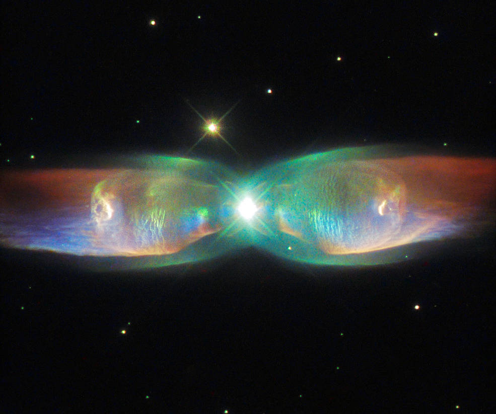The shimmering colors visible in this NASA/ESA Hubble Space Telescope image show off the remarkable complexity of the Twin Jet Nebula. Image Credit: ESA/Hubble & NASA, Acknowledgement: Judy Schmidt