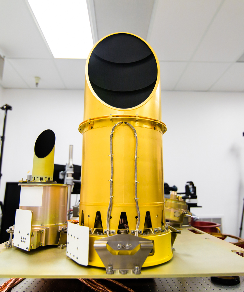 The University of Arizona's camera suite, OCAMS, sits on a test bench that mimics its arrangement on the OSIRIS-REx spacecraft. The three cameras that compose the instrument – MapCam (left), PolyCam and SamCam – are the eyes of NASA's OSIRIS-REx mission. Image Credit: University of Arizona/Symeon Platts
