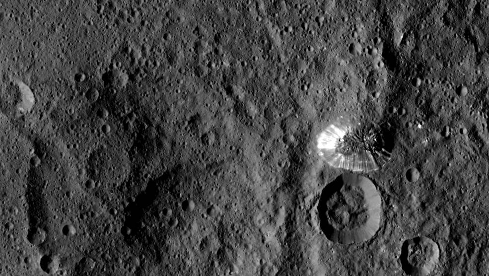 NASA's Dawn spacecraft spotted this tall, conical mountain on Ceres from a distance of 915 miles (1,470 kilometers). The mountain, located in the southern hemisphere, stands 4 miles (6 kilometers) high. Its perimeter is sharply defined, with almost no accumulated debris at the base of the brightly streaked slope. Image Credit: NASA/JPL-Caltech/UCLA/MPS/DLR/IDA