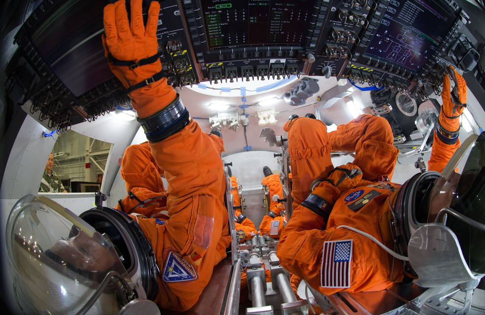 Spacesuit engineers demonstrate how four crew members would be arranged for launch inside the Orion spacecraft, using a mockup of the vehicle at Johnson Space Center. Image Credit: NASA/Robert Markowitz