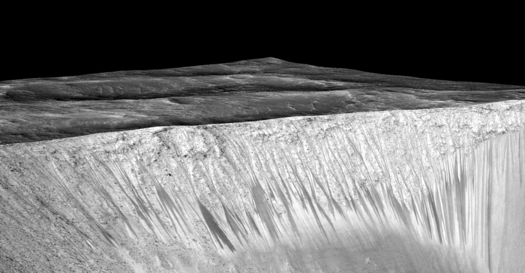 Dark narrow streaks called recurring slope lineae emanating out of the walls of Garni crater on Mars. The dark streaks here are up to few hundred meters in length. Image Credit: NASA/JPL/University of Arizona