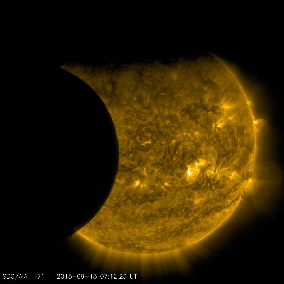 NASA's Solar Dynamics Observatory captured this image of Earth and the moon transiting the sun together on Sept. 13, 2015. The edge of Earth, visible near the top of the frame, appears fuzzy because Earth's atmosphere blocks different amounts of light at different altitudes. On the left, the moon's edge is perfectly crisp, because it has no atmosphere. This image was taken in extreme ultraviolet wavelengths of 171 angstroms. Though this light is invisible to our eyes, it is typically colorized in gold. Image Credit: NASA/SDO
