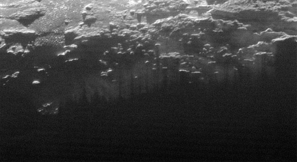 Near-Surface Haze or Fog on Pluto: In this small section of the larger crescent image of Pluto, taken by NASA's New Horizons just 15 minutes after the spacecraft's closest approach on July 14, 2015, the setting sun illuminates a fog or near-surface haze, which is cut by the parallel shadows of many local hills and small mountains. The image was taken from a distance of 11,000 miles (18,000 kilometers), and the width of the image is 115 miles (185 kilometers). Image Credit: NASA/JHUAPL/SwRI